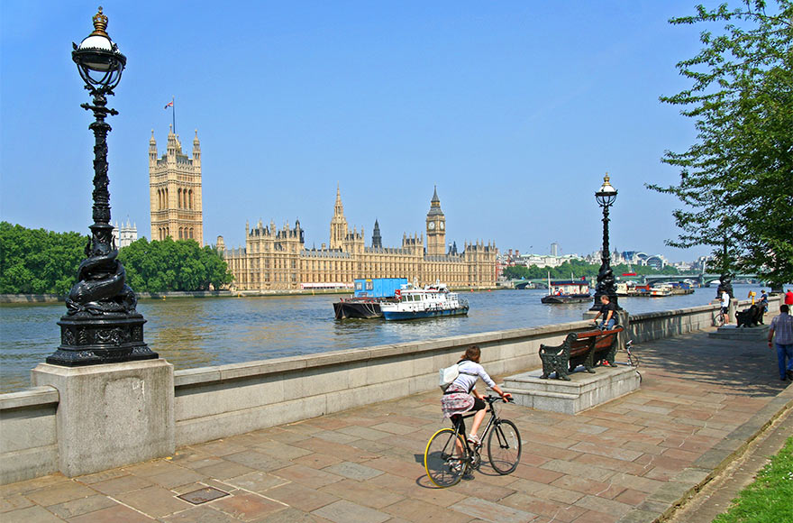 Lady cycling alongside the Thames, Palace of Westminster and boats in the background