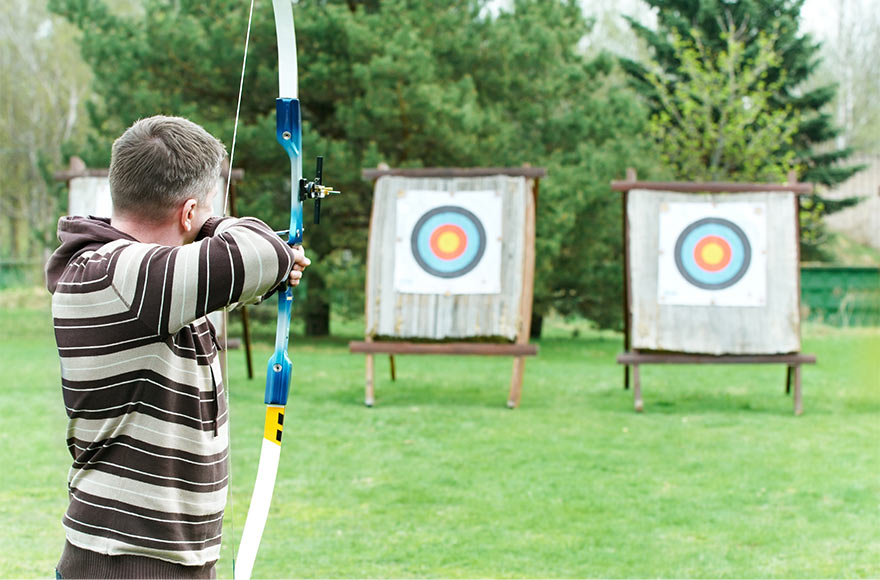 Man in striped hoodie aiming bow and arrow at a target in green open space