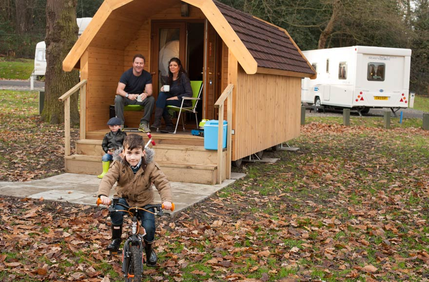 Child riding a bike while family watch from camping pod