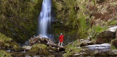 Onlooker admiring Pistyll Rhaeadr waterfall in Wales