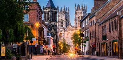 Road leading to York Cathedral, with buildings and shops lining streets