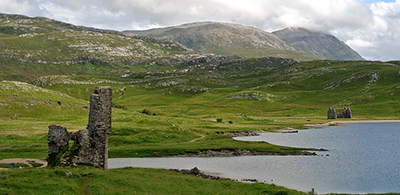 Remains of Ardvreck Castle amid mountain backdrop