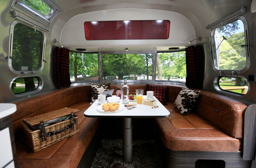The lounge area has soft leather seats and is surrounded by large wrap-around windows