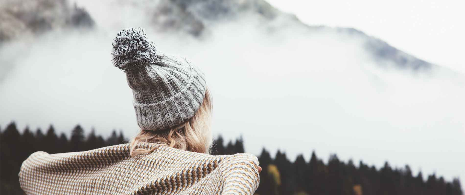 Girl staying warm in wintry setting wearing a knitted bobble hat