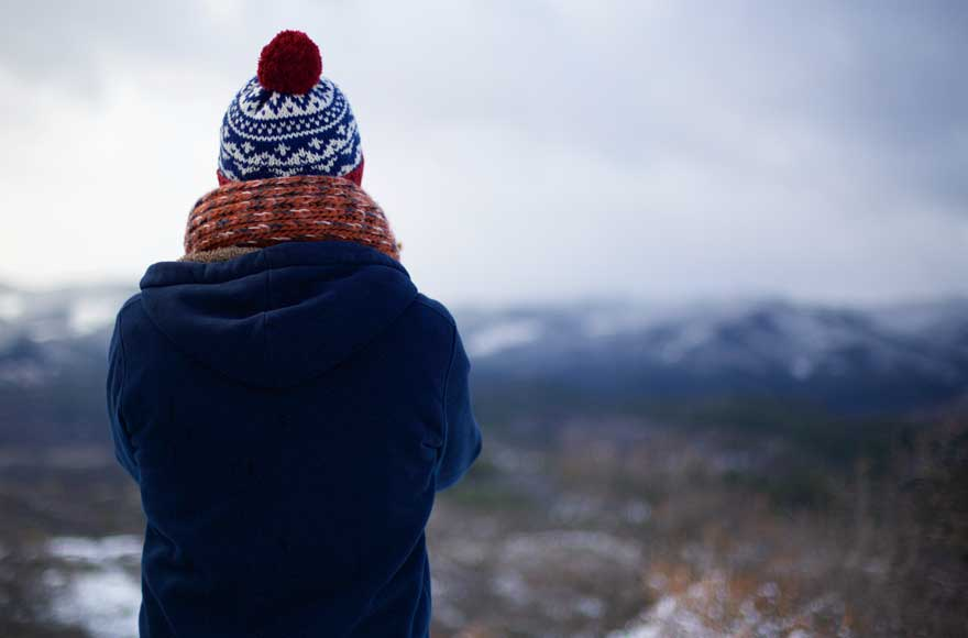 Person in hat and scarf looking out over wintry scenes