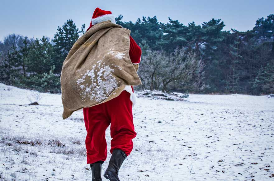 Santa carrying his sack of presents over snowy grass