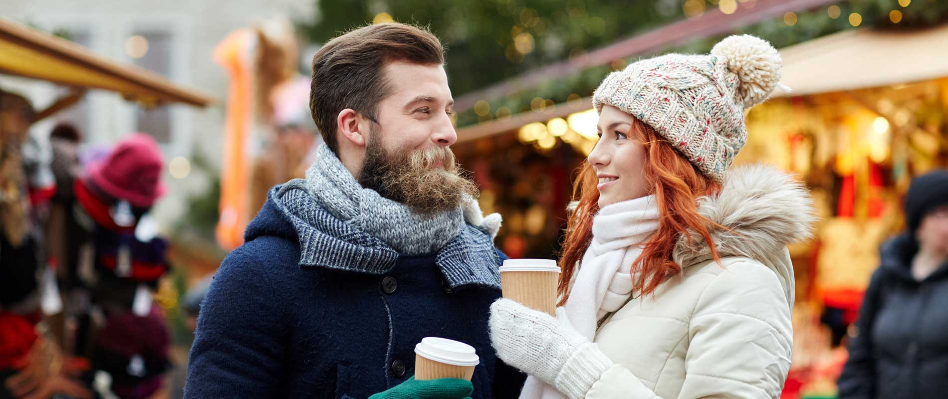 Young couple wearing coats and scarves enjoying coffees at a Christmas market