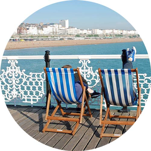 Couple sitting on deck chairs on Brighton Pier, East Sussex