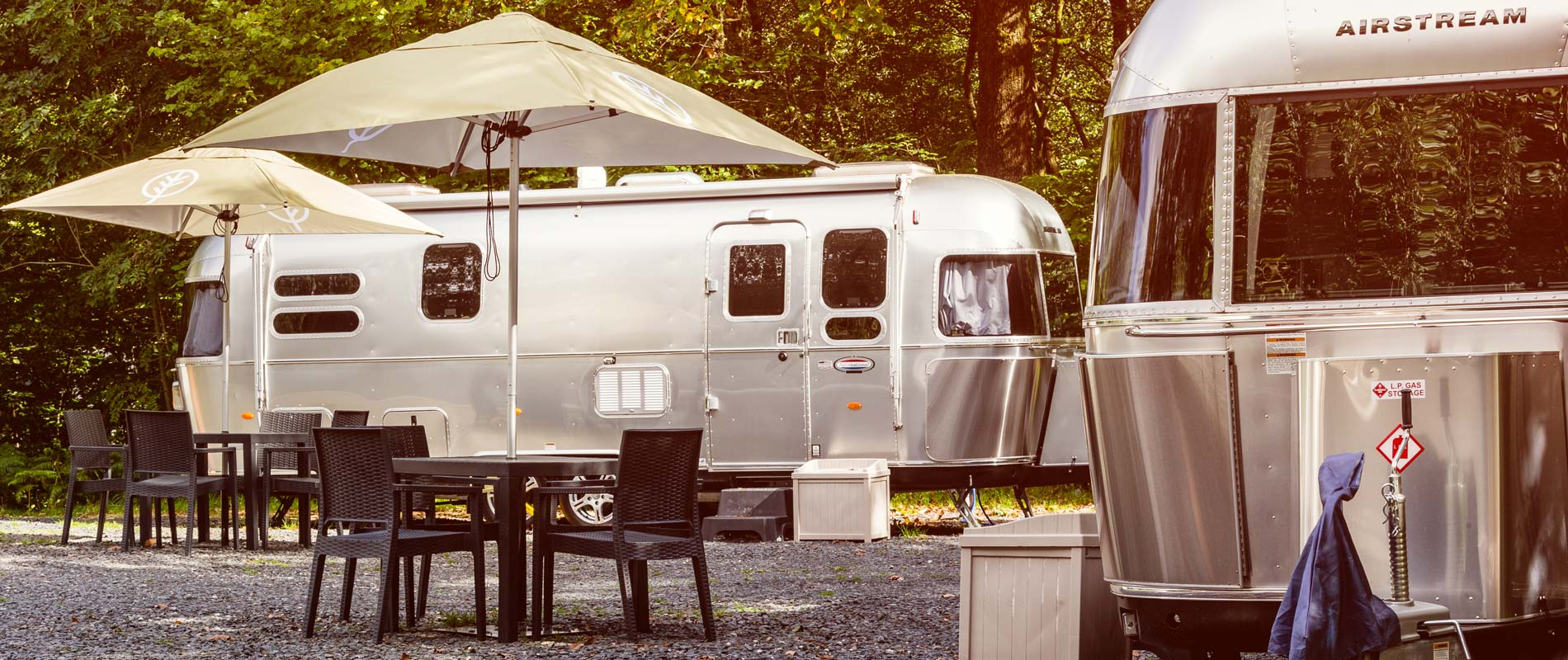 Two airstreams with outdoor seating, parasols and trees in background