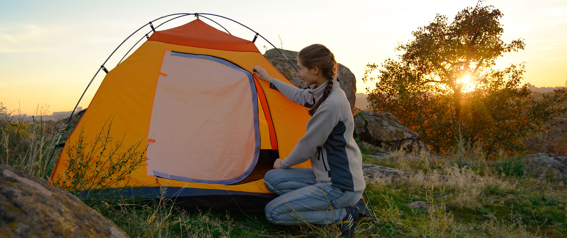 Girl putting up a tent surrounded by nature