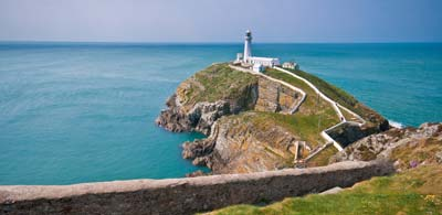 South Stack Lighthouse upon rocky peninsula overlooking sea