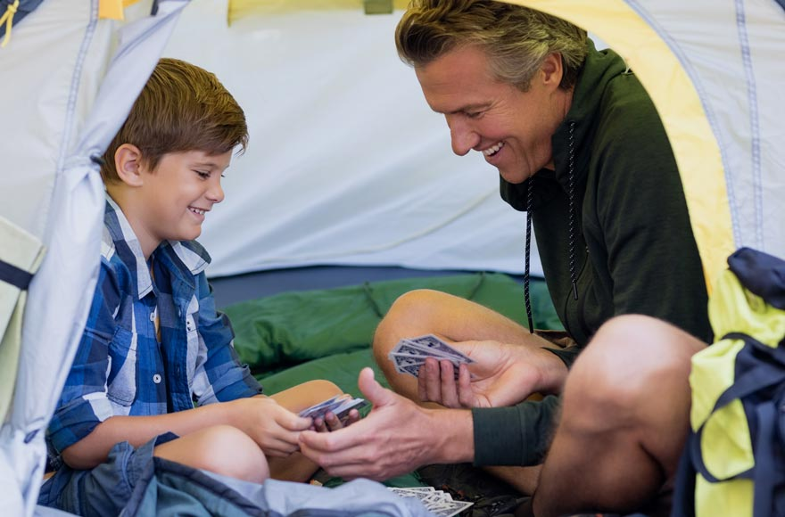 Father and son playing card game in their tent while it rains outside