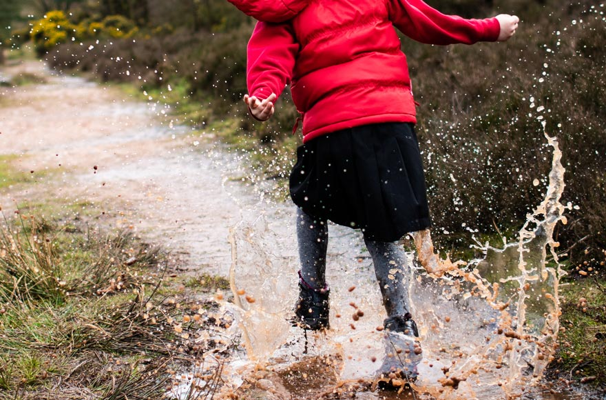 Young girl splashing around in puddles on a muddy path, wearing wellington boots