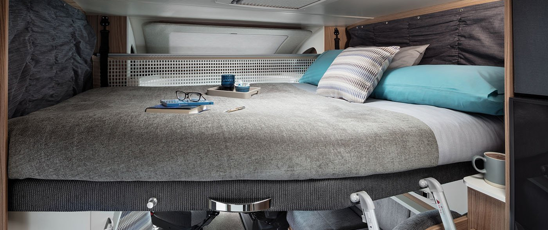 Suspended bed inside hired motorhome, with books and reading glasses on mattress