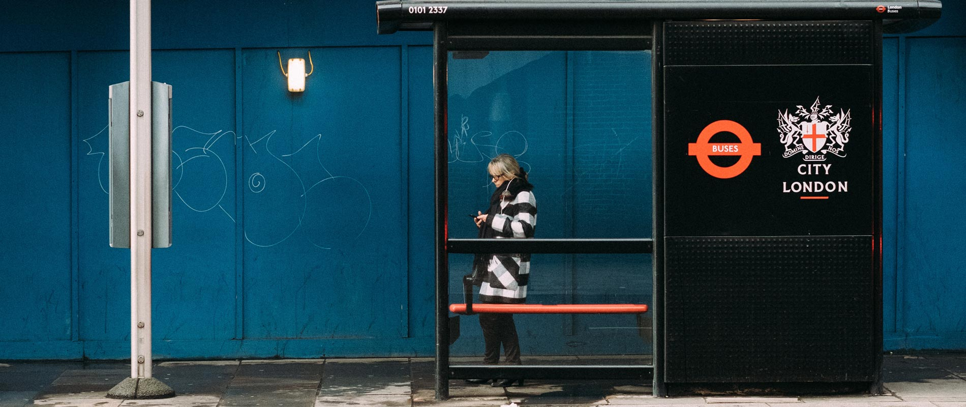 lady waiting at a bus stop in London