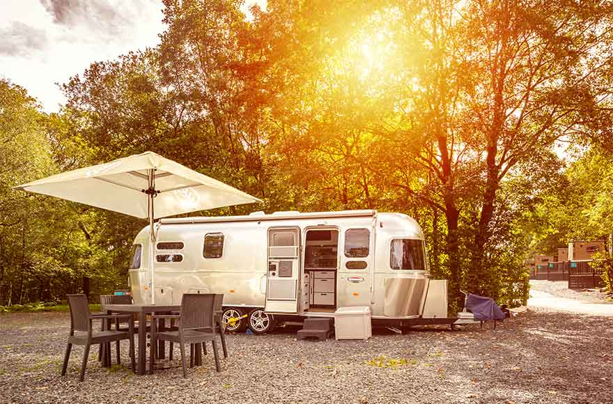 Silver airstream caravan with outdoor seating, with sun setting