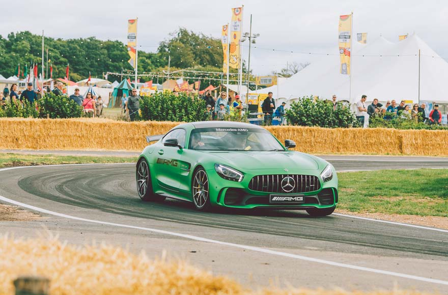 A green car spins round the track at CarFest