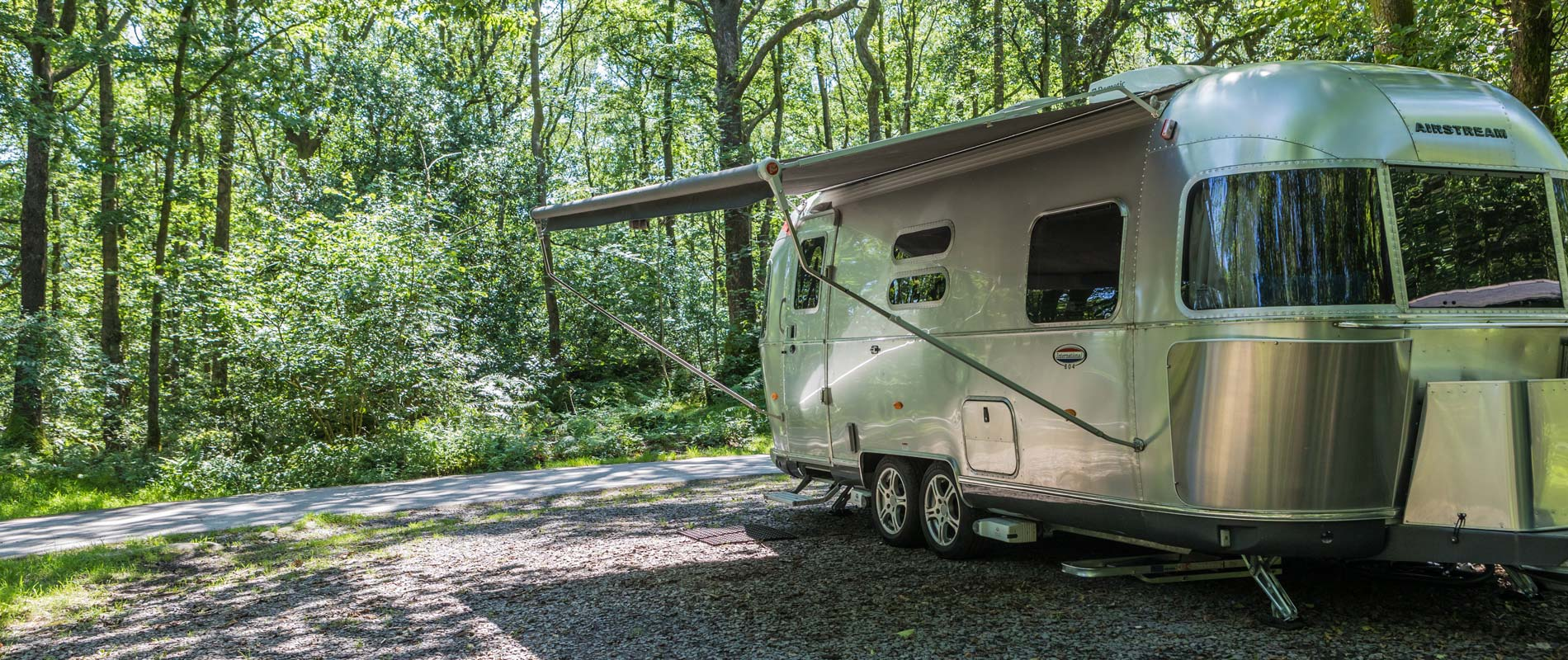 Classic airstream in wooded area with extending awning