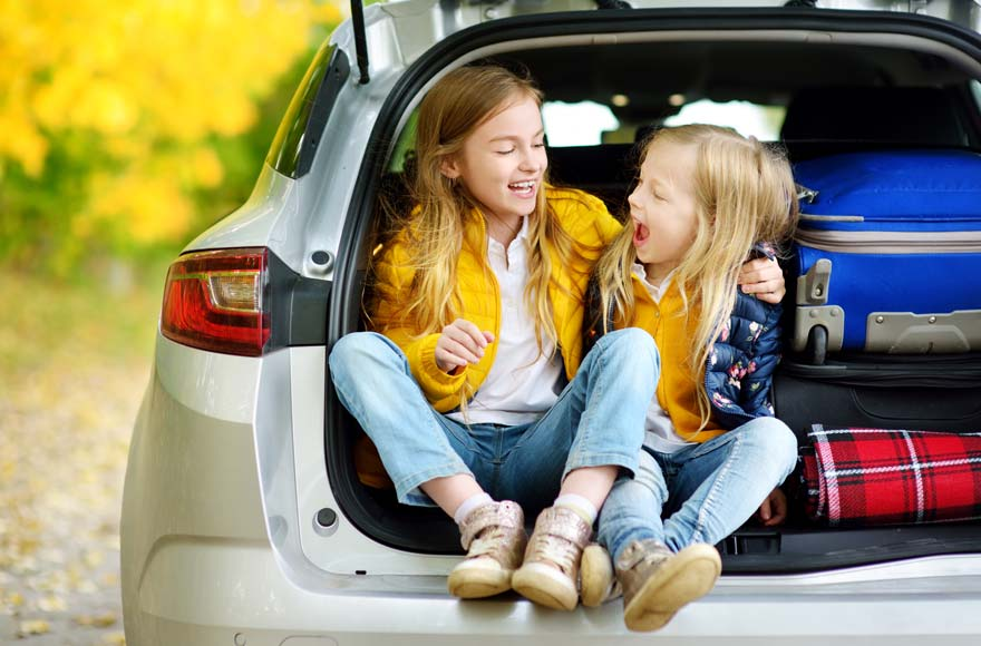 Young girls wearing yellow in the boot of a car