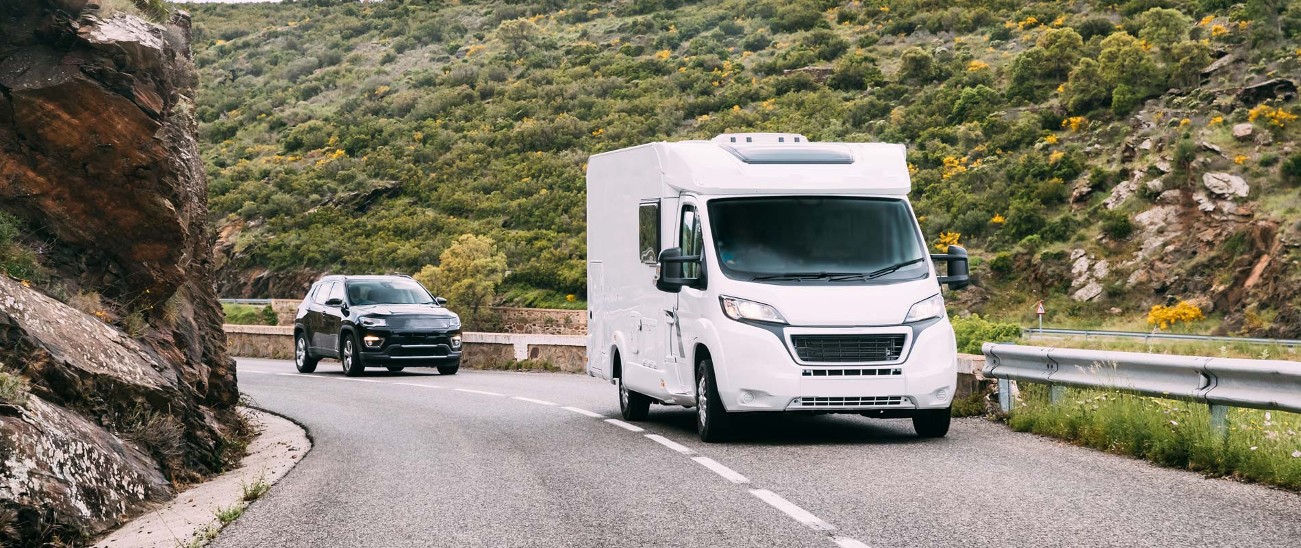Hired motorhome driving on main road in country valley
