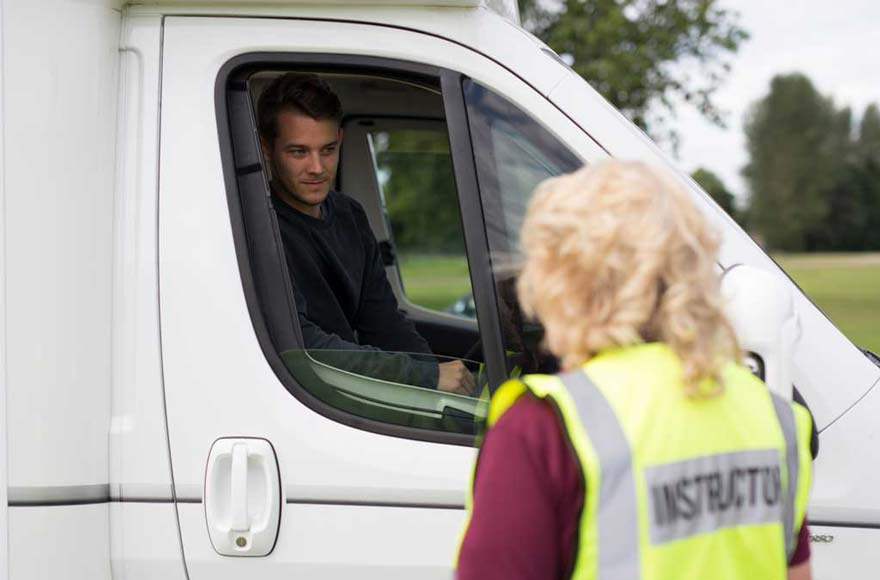 Beginner talking to motorhome course instructor from driver's seat