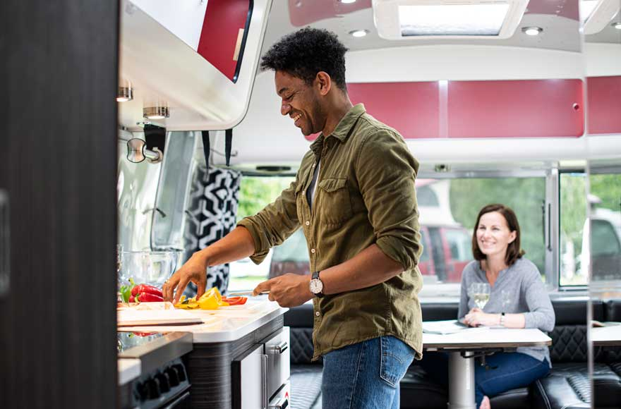 Man cooking in airstream kitchen while chatting to wife