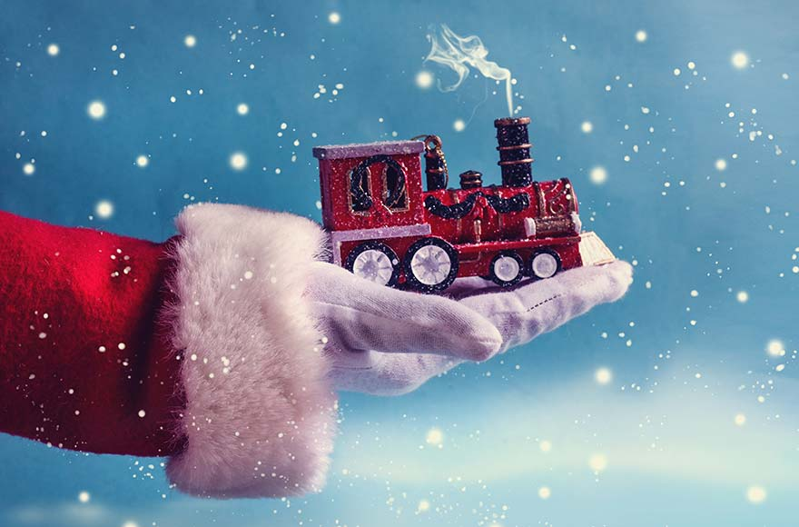 Gloved hand holding a small red train in snowy setting