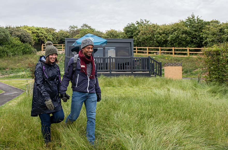Couple walking outside a glamping pod at the Experience Freedom Brighton site