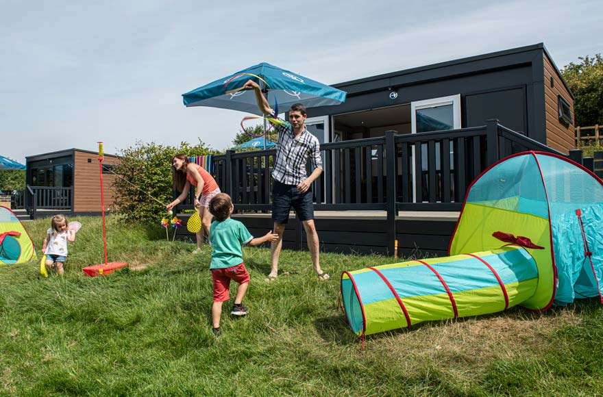 young family playing outside glamping pod at Brighton