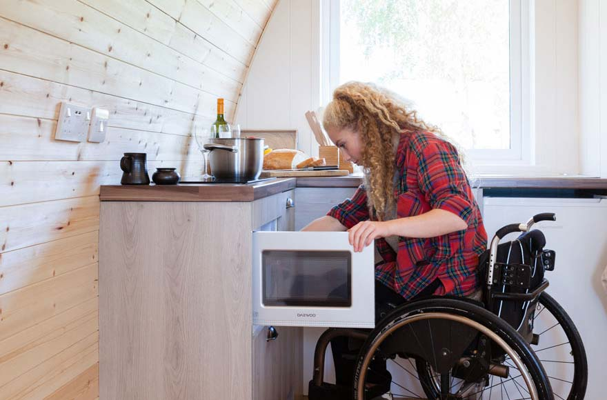 Female wheelchair user using microwave in accessible glamping pod