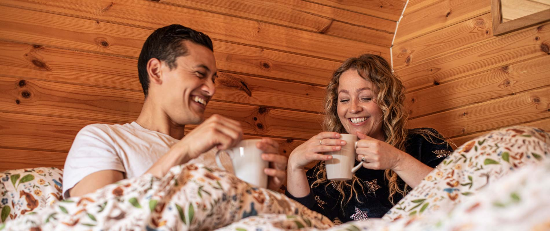 Couple under duvet in wooden-interior glamping pod