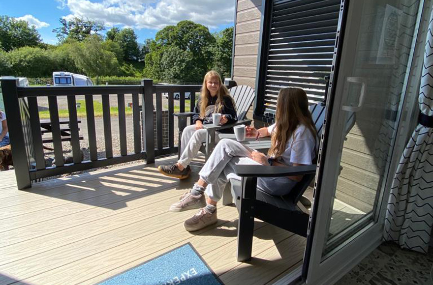 Two girls chatting on wooden bench outside accommodation